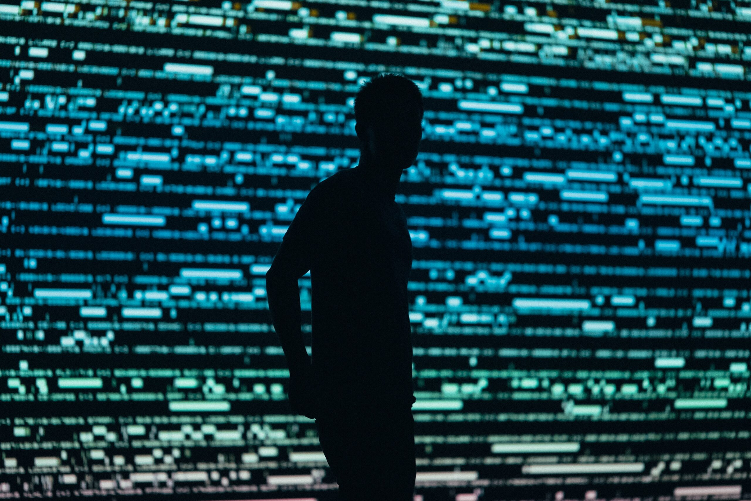 man backlit with glowing data screen